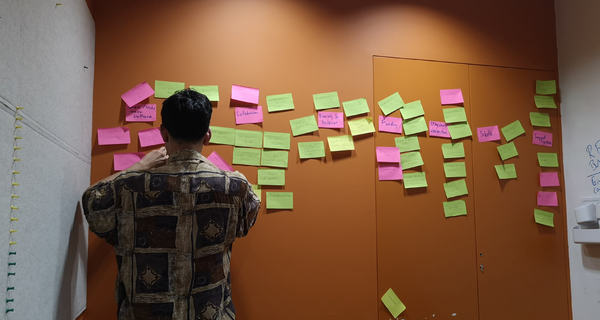 A man stands in front of a wall covered with sticky notes