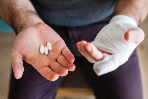 A man holds tablets with one hand in bandages
