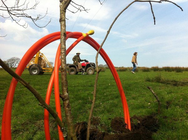 Broadband cables on farm land with tractor and people