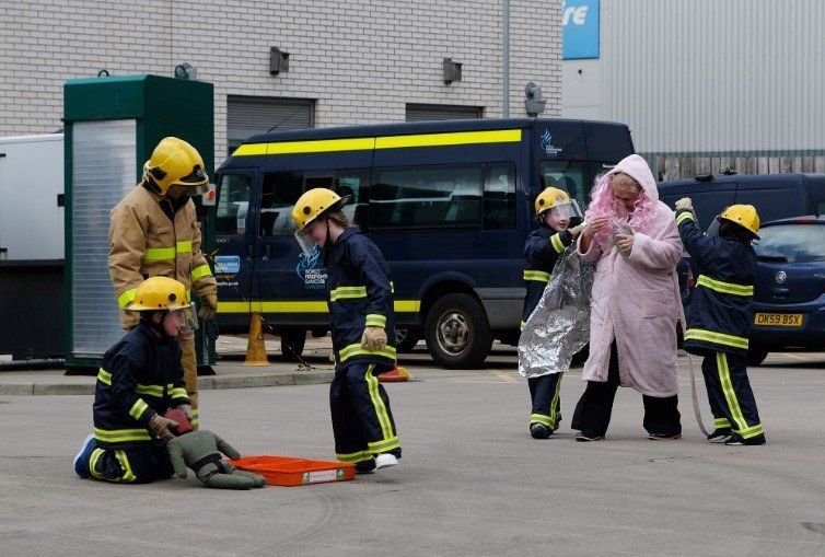 A photo of two young fire cadets receiving wisdom from a firefighter