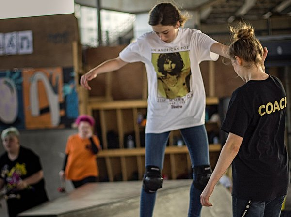 Projekts MCR skate park young woman skateboarding and instructor
