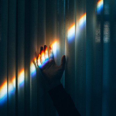 Hand in rainbow beam