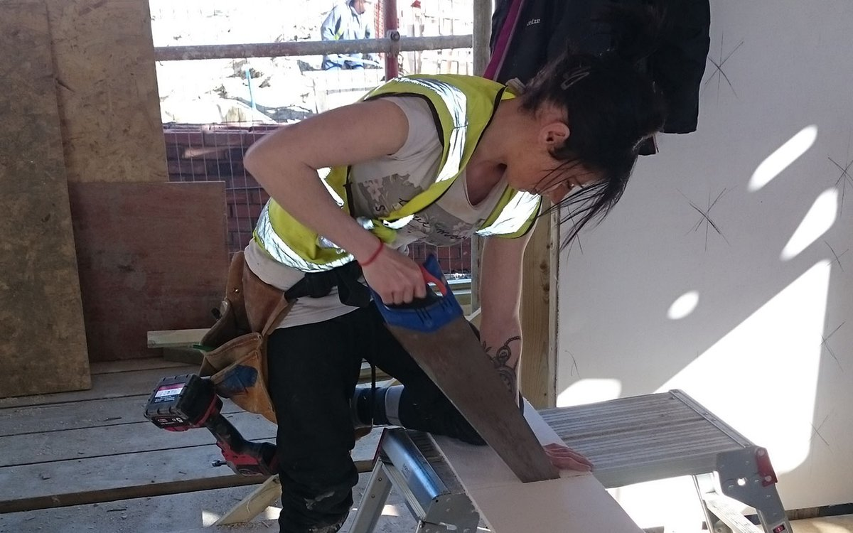 ToolShed student saws a plank of wood - Inclusive Economy Partnership