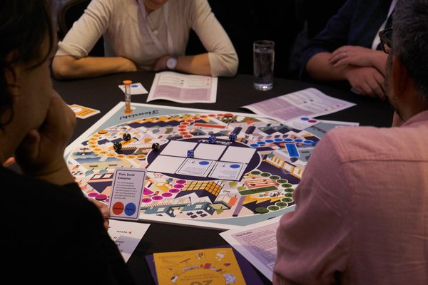 Flourish! board game people playing game at tables 3