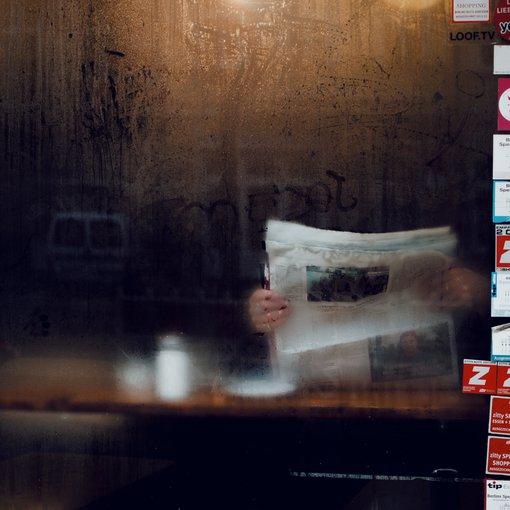 Person reading newspaper through raining window