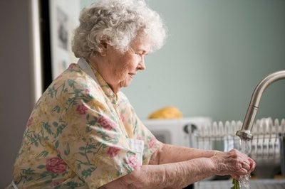 Older woman washes hands at tap