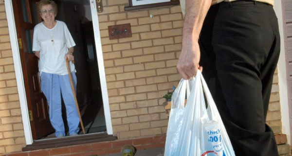client-greeting-care-in-the-home-volunteer-as-he-brings-her-shopping-uk-015-3.jpg