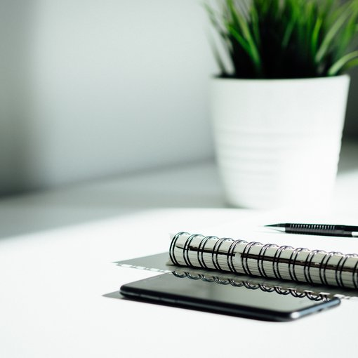 A phone and notebook with pen
