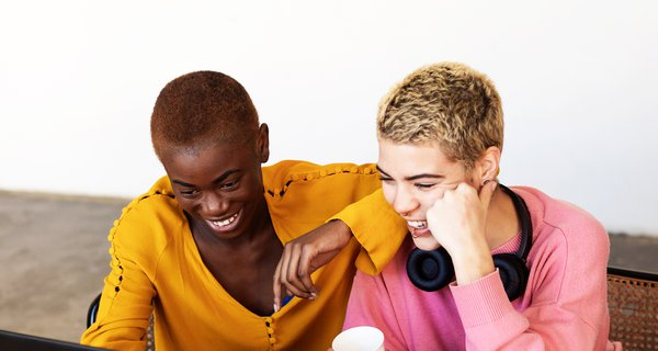 Two people at laptop laughing