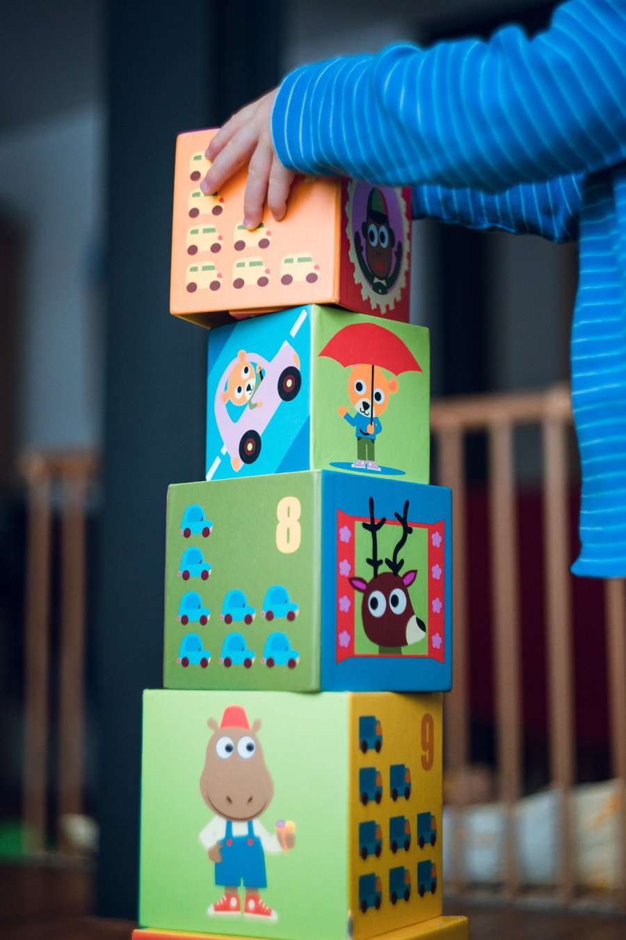 Child stacks colourful blocks on top of one another