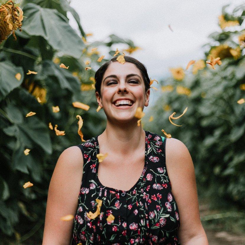 Woman walks through sunflower field